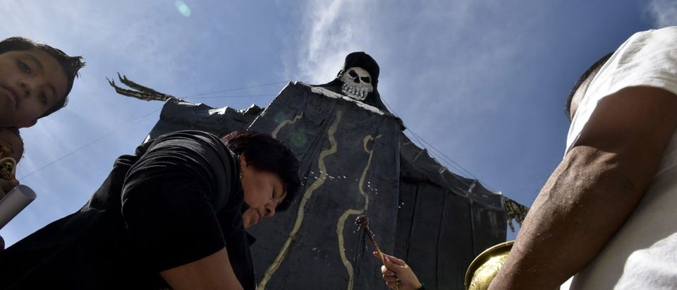 """TOPSHOT - Devotees of the Santa Muerte (Holy Death) are blessed by Enriqueta Vargas (unseen) known as """"La Madrina"""" (The Godmother) during a celebration at a sanctuary in Santa Maria Cuautepec, Tultitlan, Mexico on February 7, 2016. (YURI CORTEZ/AFP/Getty Images)"""