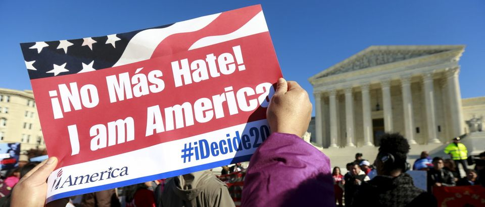 A protester holds her sign up as immigrants and community leaders rally in front of the U.S. Supreme Court on Nov. 20, 2015. (REUTERS/Kevin Lamarque)