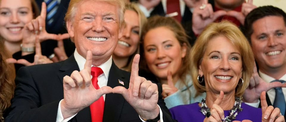 "U.S. President Donald Trump and Education Secretary Betsy DeVos make ""U"" symbols with their hands while posing with the Utah Skiing team as they greet members of Championship NCAA teams at the White House in Washington, U.S., Nov. 17, 2017. REUTERS/Joshua Roberts"