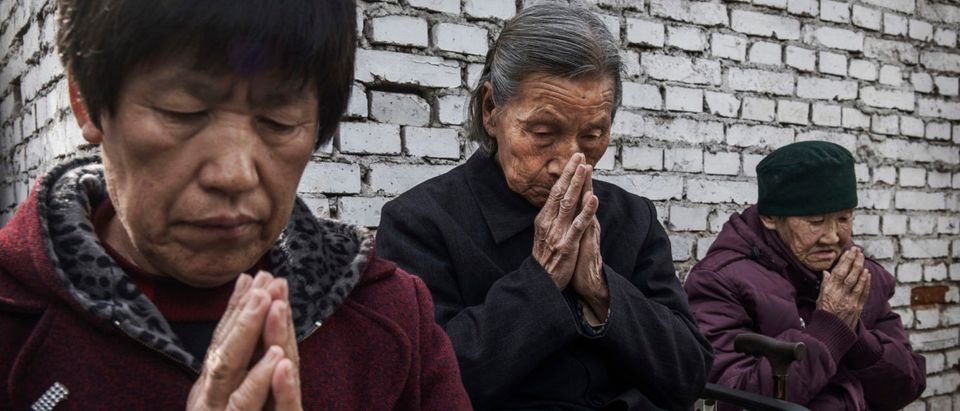 """SHIJIAZHUANG, CHINA - APRIL 09: (CHINA OUT) Chinese Catholic worshippers pray at the Palm Sunday Mass during the Easter Holy Week at an """"underground"""" or """"unofficial"""" church on April 9, 2017 near Shijiazhuang, Hebei Province, China. (Photo by Kevin Frayer/Getty Images)"""