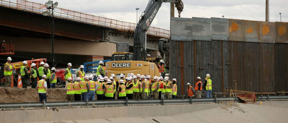 Workers and U.S border patrol officers stand next to an excavator working in a section of the new wall between El Paso and Ciudad Juarez