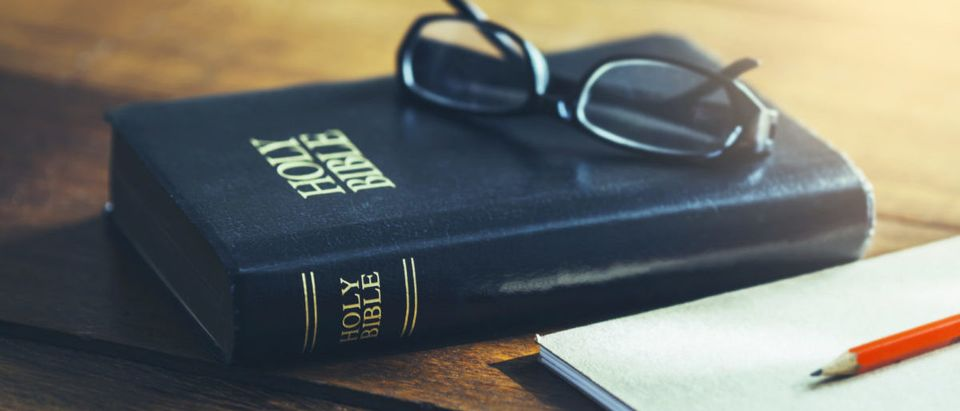 Holy Bible with eye glasses and note book, pencil on wooden table with window light in the morning, copy space. - Freedom Studio via Shutterstock