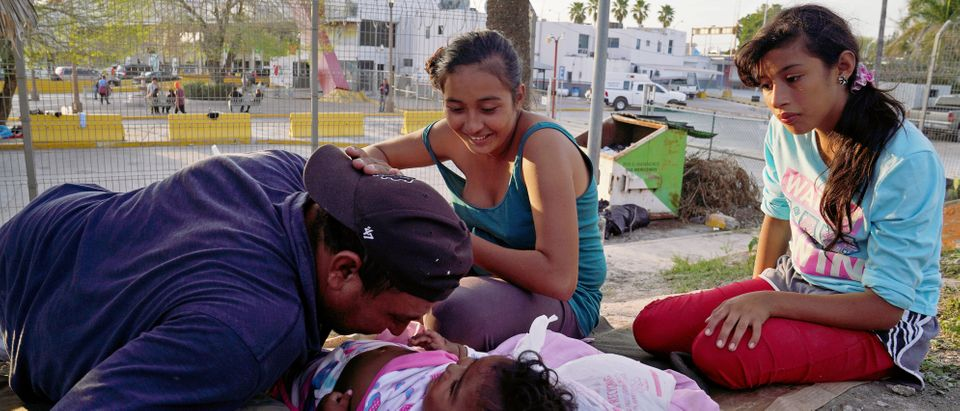 Asylum seekers wait near the Matamoros and Brownsville International Bridge in Matamoros