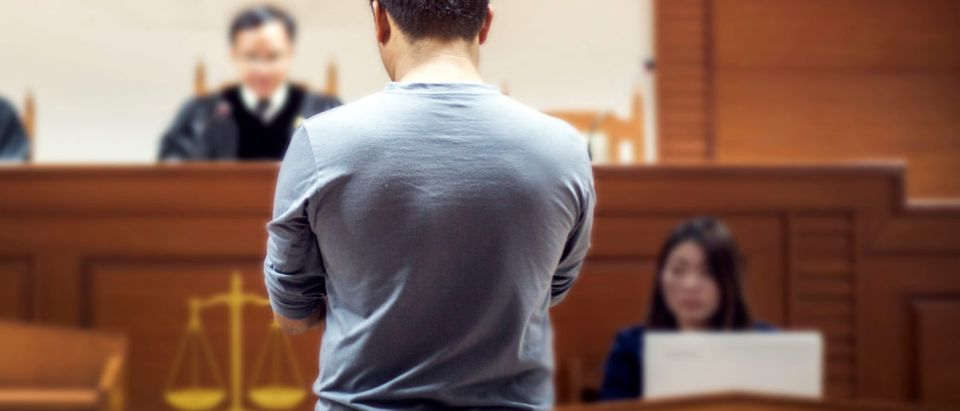 Back of man talking to magistrate in court. Shutterstock