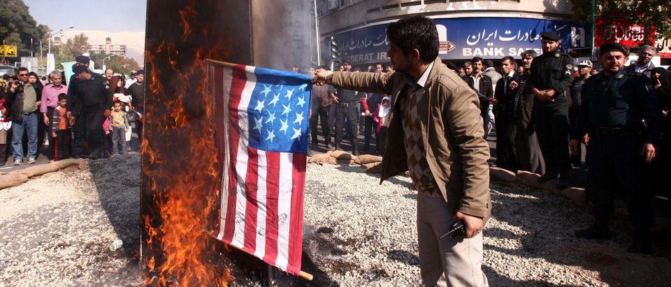Iranian men burn a US flag outside the f