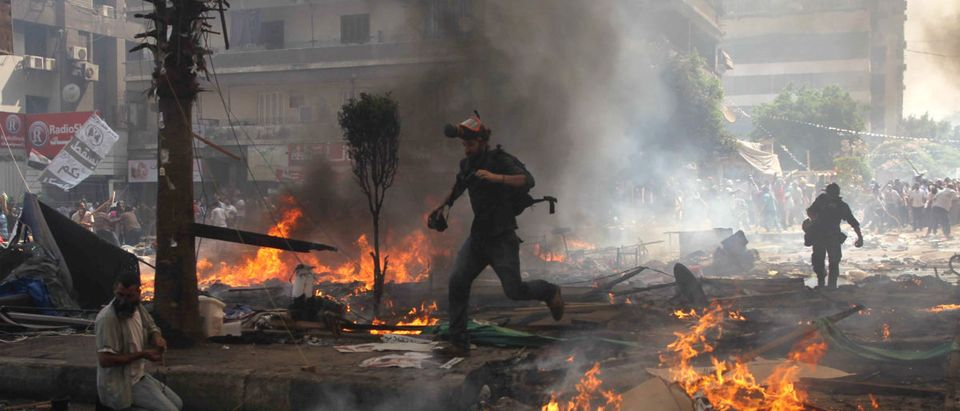 Reporters run for cover during clashes between Muslim Brotherhood supporters and police in Cairo.