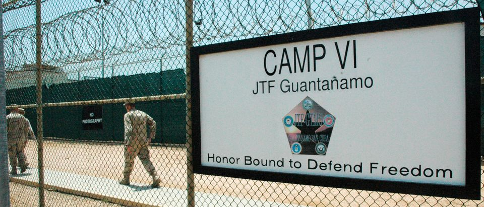 U.S. Navy guards walk inside fencing of Camp VI, the maximum security detention facility for terrorism suspects at the U.S. Naval Base at Guantanamo Bay, Cuba, July 23, 2008. The U.S. military invited news media members to view the facility on Wednesday. Picture taken on July 23, 2008. REUTERS/Randall Mikkelsen (CUBA)