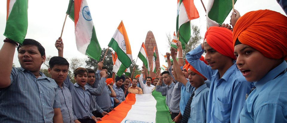 Students hold a giant Indian national flag during a ceremony to pay homage at the Jallianwala Bagh memorial to mark 100th anniversary of Jallianwala Bagh massacre in Amritsar