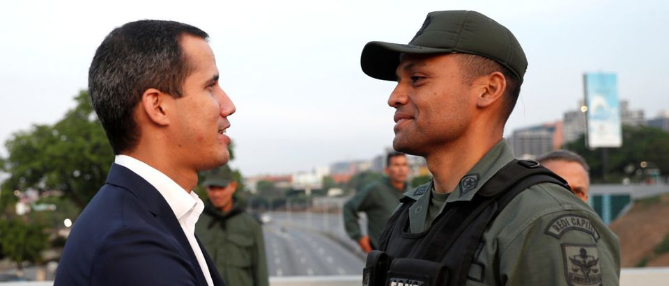 "Venezuelan opposition leader Juan Guaido, who many nations have recognised as the country's rightful interim ruler, shakes hands with a military member near the Generalisimo Francisco de Miranda Airbase ""La Carlota"", in Caracas, Venezuela April 30, 2019. REUTERS/Carlos Garcia Rawlins"