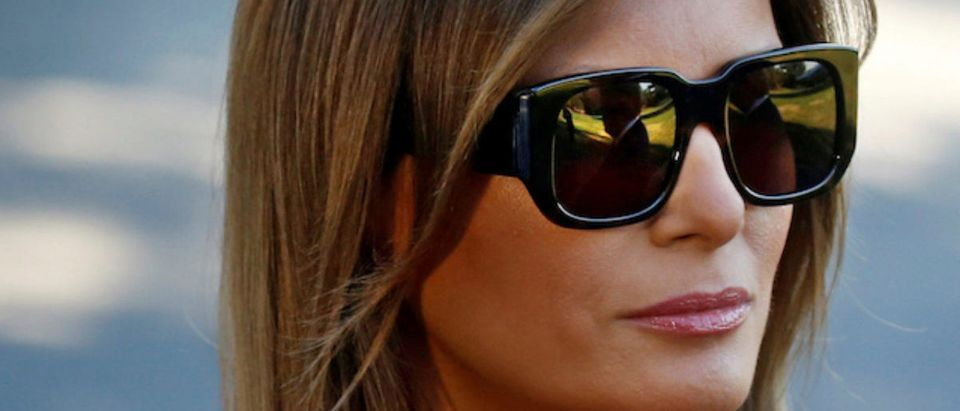 U.S. first lady Melania Trump stands beside U.S. President Donald Trump (Relected in sunglasses) as he speaks with the news media before boarding Marine One for travel to Europe from the White House, in Washington, U.S., July 10, 2018. REUTERS/Leah Millis