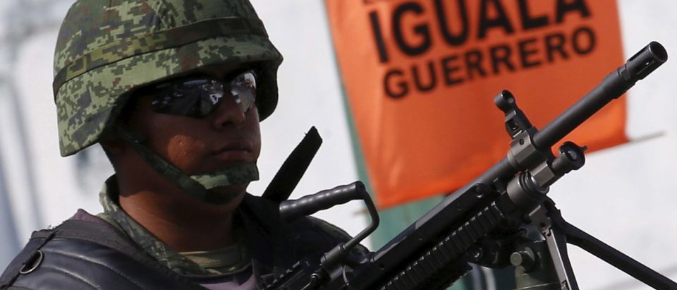 Soldier stands guard atop a vehicle during the Flag Day ceremony in Iguala