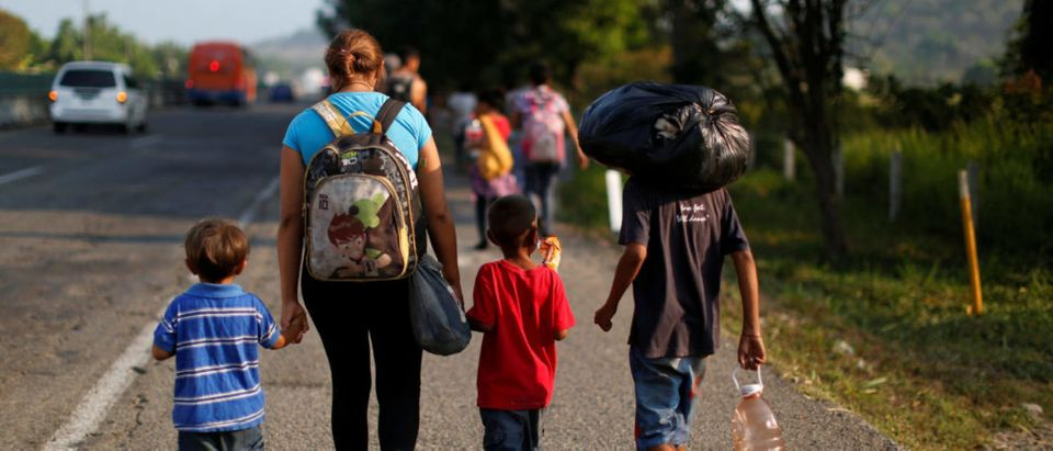 A migrant mother and her children walk along a road with other Central American migrants during their journey towards the United States, in Tuzantan