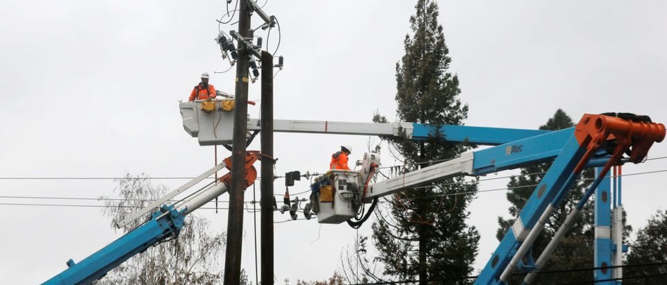 PG&E crew work on power lines to repair damage caused by the Camp Fire in Paradise, California, U.S. November 21, 2018. REUTERS/Elijah Nouvelage