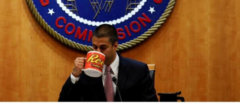 FILE PHOTO: Chairman Ajit Paid drinks coffee ahead of the vote on the repeal of so called net neutrality rules at the Federal Communications Commission in Washington, U.S., December 14, 2017. REUTERS/Aaron P. Bernstein/File Photo