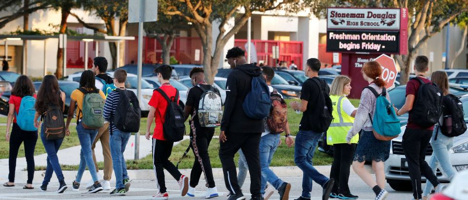 Students cross a street to enter for the first day of classes at Marjory Stoneman Douglas High School in Parkland