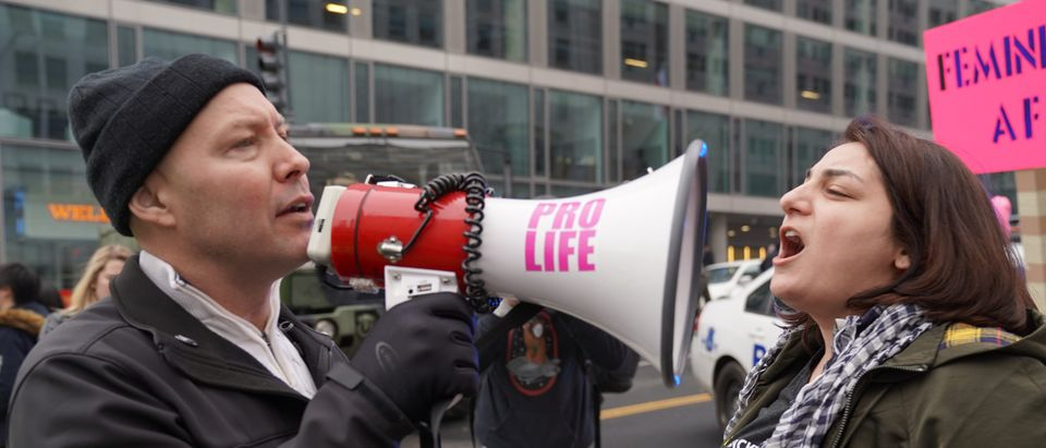 January 19, 2019: An abortion supporter shouts into a bull horn of an anti-abortion activist under police protection at the 2019 Women's March. Shutterstock/Phil Pasquini