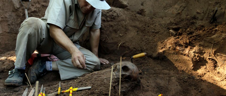 "A member of the police assists Argentine forensic expert Rogelio Agustin Goiburu of human rights group ""Verdad, Justicia y Reparacion"" to excavate human remains discovered in the grounds of a police barracks in Asuncion"