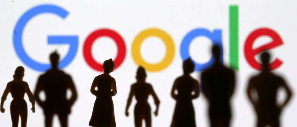 Small toy figures are seen in front of Google logo in this illustration picture