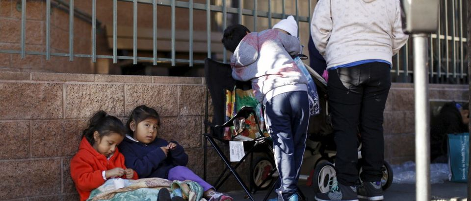 Children sit on a piece of cardboard as they wait in line for an early Thanksgiving meal served to the homeless at the Los Angeles Mission in Los Angeles