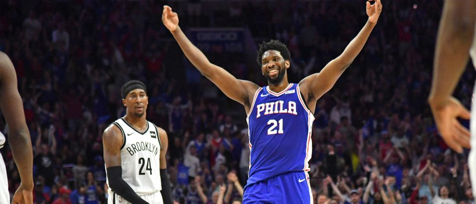Joel Embiid (21) reacts after making a three-point shot