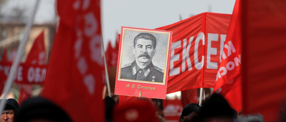 A supporter of the Russian Communist Party carries a board with a portrait of Soviet leader Joseph Stalin during a procession to celebrate the Defender of the Fatherland Day, which was before known as Soviet Army and Navy Day, in Moscow, Russia February 23, 2019. REUTERS/Maxim Shemetov