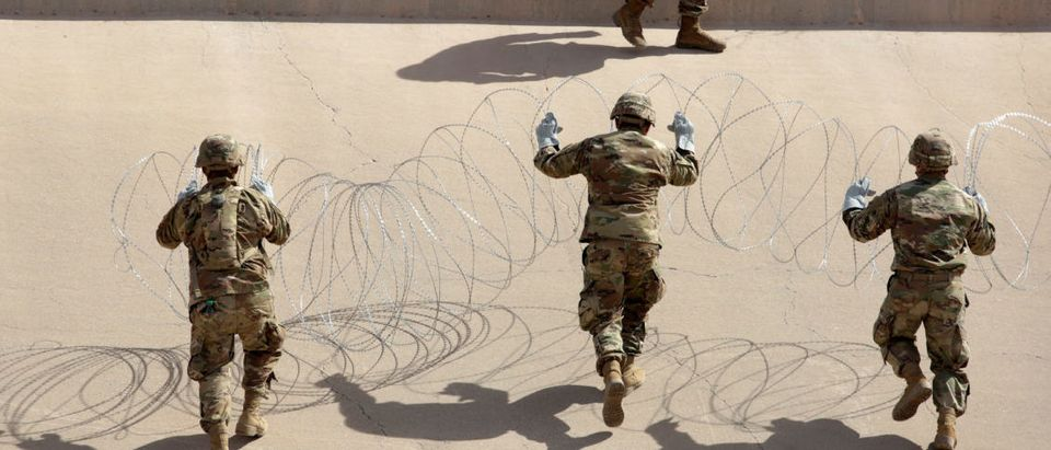 U.S. soldiers install concertina wire next to the border fence between Mexico and the United States, in El Paso, Texas, U.S., in this picture taken from Ciudad Juarez