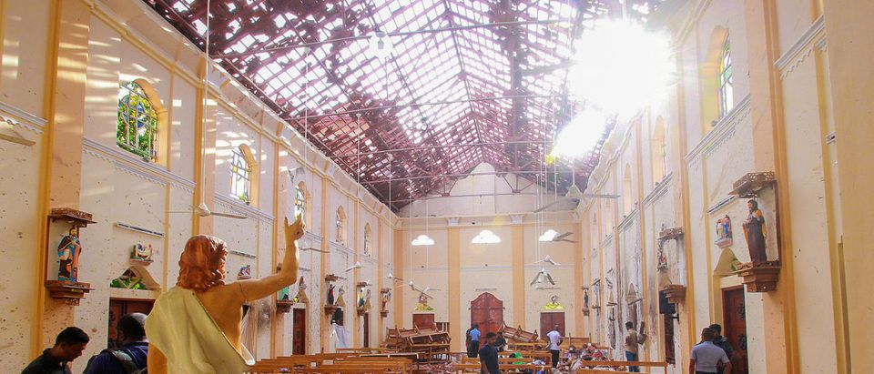 A blood-spattered statue of Jesus Christ is pictured while crime scene officials inspect the site of a bomb blast, as the sun shines through the blown-out roof, inside St Sebastian's Church in Negombo, Sri Lanka, April 21, 2019. REUTERS/Stringer