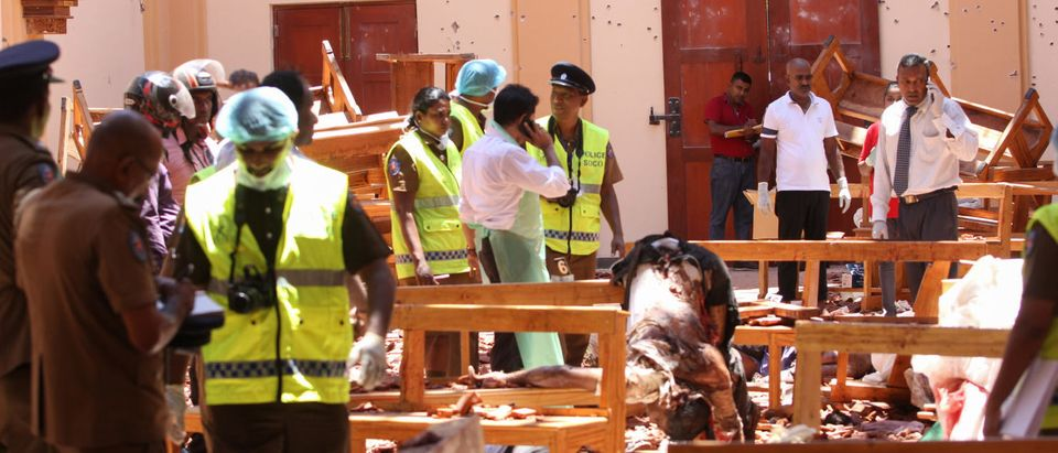 Sri Lankan security personnel walk past debris next to a dead body slumped over a bench following an explosion in St Sebastian's Church in Negombo, north of the capital Colombo, on April 21, 2019. (STR/AFP/Getty Images)