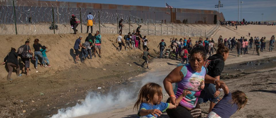 Maria Meza, a 40-year-old migrant woman from Honduras, part of a caravan of thousands from Central America trying to reach the United States, runs away from tear gas with her five-year-old twin daughters Saira Mejia Meza (L) and Cheili Mejia Meza (R) in front of the border wall between the U.S and Mexico, in Tijuana, Mexico November 25, 2018. REUTERS/Kim Kyung-hoon