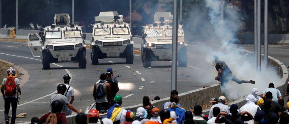 "Opposition demonstrators face military vehicles near the Generalisimo Francisco de Miranda Airbase ""La Carlota"" in Caracas"