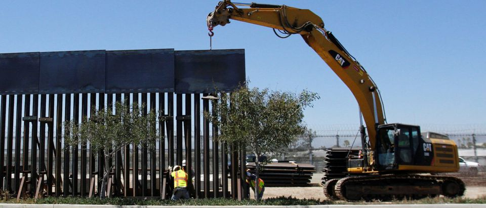 Construction workers replace a section of the old Mexico-U.S. border as seen from Tijuana
