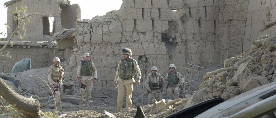 U.S. troops search through the rubble of a house destroyed in an explosion in the village of Qala-e-Gulai near the US-led coalition's Bagram Air Base headquarters north of Kabul, Oct. 3, 2003. (Photo by SHAH MARAI/AFP/Getty Images)
