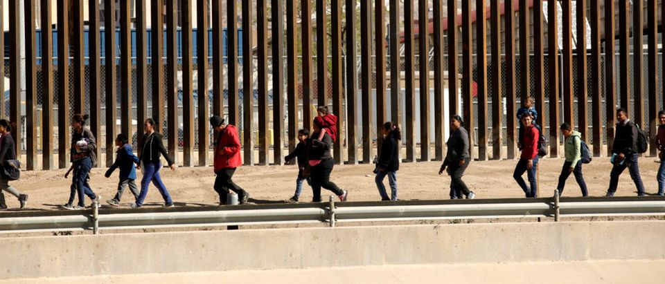 Migrants are escorted by U.S. Customs and Border Protection (CBP) officials (not pictured) after crossing illegally into the United States to request asylum, in El Paso, Texas, U.S., in this picture taken from Ciudad Juarez