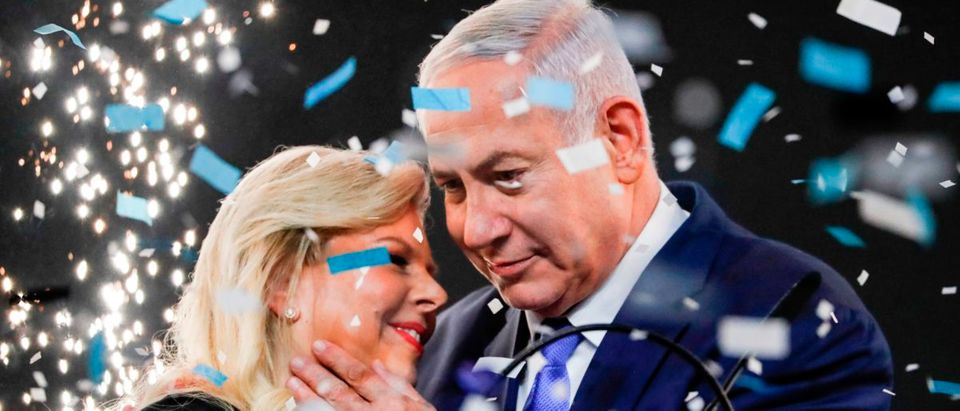 Israeli Prime Minister Benjamin Netanyahu embraces his wife Sara as confetti and fireworks are blown during his appearance before supporters at his Likud Party headquarters in the Israeli coastal city of Tel Aviv on election night early on April 10, 2019. (THOMAS COEX/AFP/Getty Images)