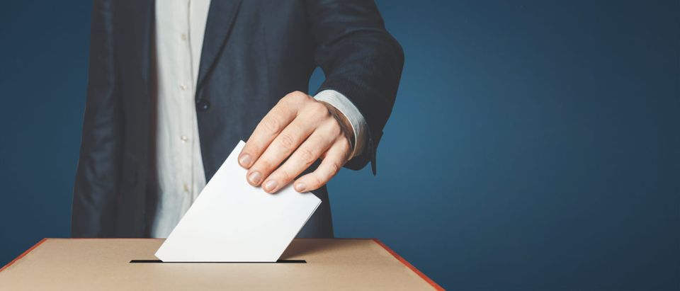 Man Voter Putting Ballot Into Voting box. Democracy Freedom Concept [Shutterstock]