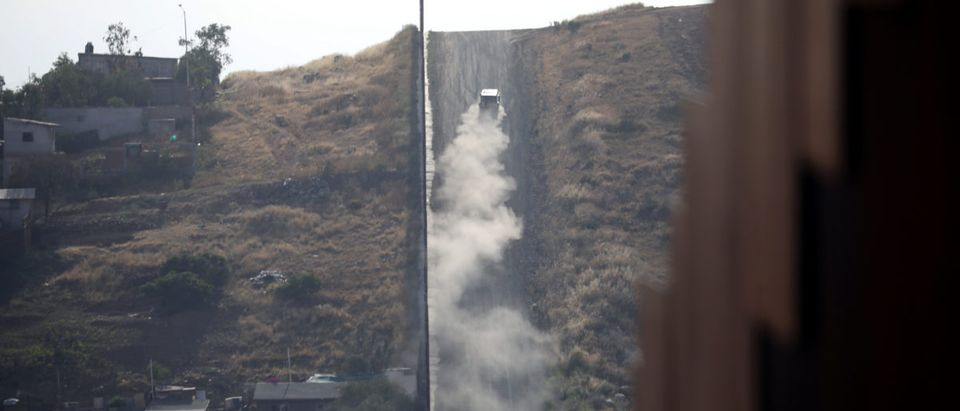 A U.S. Border Patrol car drives next to the border fence between U.S. and Mexico, as seen from Tijuana
