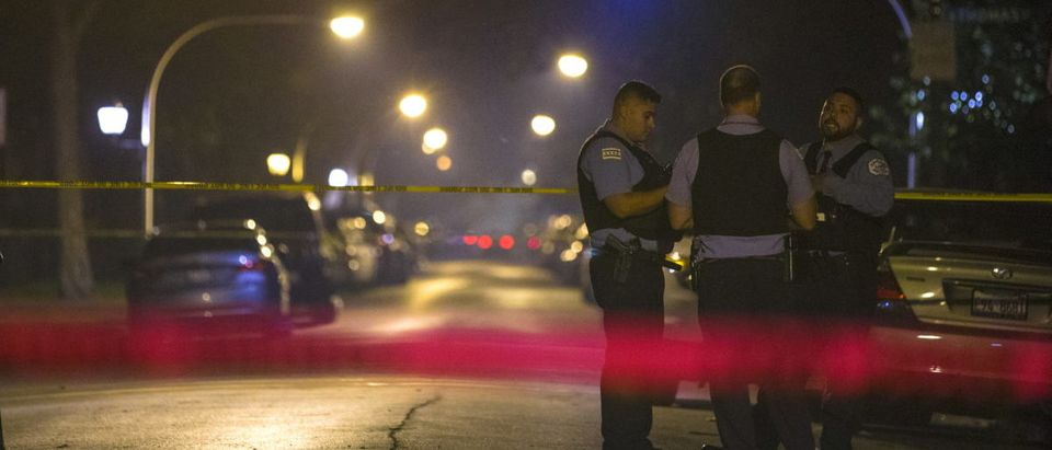Chicago police officers investigate a crime scene where 7-year-old Amari Brown was shot and killed in Chicago
