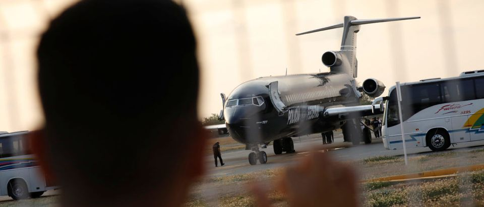 A man looks at a Mexican Federal Police plane as Cuban migrants are deported, in the airport of Tapachula