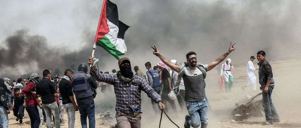 "Palestinian protesters pull a metal cable as they try to take down a section of barbed wire during clashes with Israeli forces on April 20, 2018, east of Khan Yunis, in the southern Gaza Strip during mass protests along the border of the Palestinian enclave, dubbed ""The Great March of Return,"" which has the backing of Gaza's Islamist rulers Hamas. (SAID KHATIB/AFP/Getty Images)"