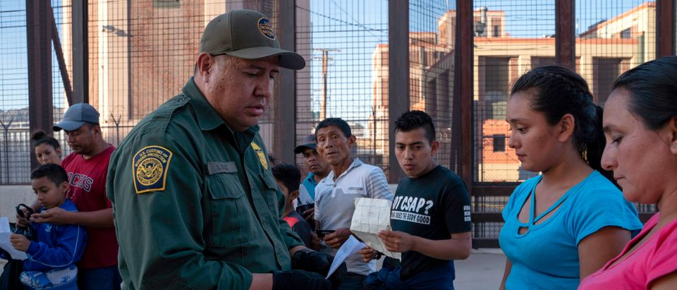 US Customs and Border Protection agent checks documents of a small group of migrants, who crossed the Rio Grande from Juarez, Mexico, on May 16, 2019, in El Paso, Texas. (PAUL RATJE/AFP/Getty Images)