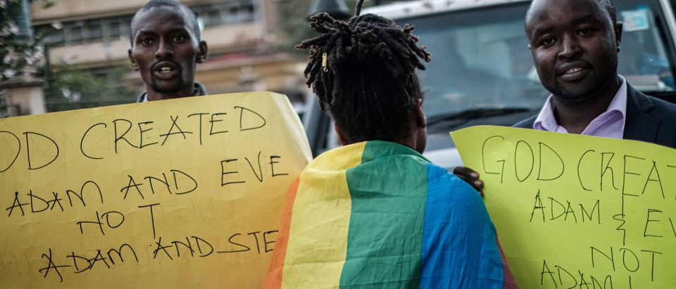 A woman wearing a rainbow flag walks between Christian members of the Sozo church of God as they hold anti-LGBTQ signs and sing against homosexuality after a verdict on scrapping laws criminalising homosexuality in front of the Milimani high court in Nairobi, Kenya, on May 24, 2019. (YASUYOSHI CHIBA/AFP/Getty Images)