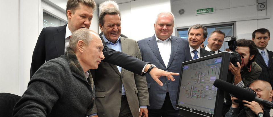 "Russian Prime Minister Vladimir Putin (L),Gazprom Chief Executive Officer Alexei Miller (2nd L) and former German chancellor Gerhard Schroeder (3rd L) look at a screen as they attend the inauguration of the Nord Stream Project information mount at the gas compressor station ""Portovaya"" outside Vyborg, September 6, 2011. ALEXEY NIKOLSKY/AFP/Getty Images)"