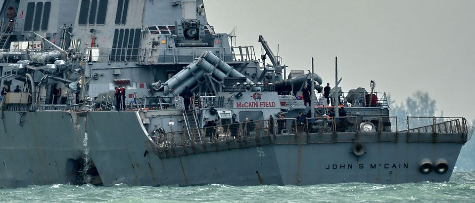 The guided-missile destroyer USS John S. McCain, with a hole on its portside after a collision with an oil tanker, makes its way to Changi naval base in Singapore on August 21, 2017. (ROSLAN RAHMAN/AFP/Getty Images)