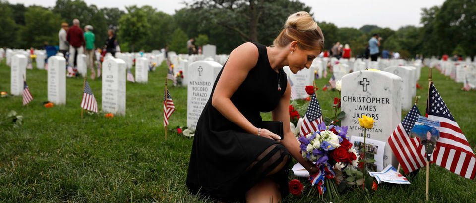 WASHINGTON, DC - MAY 27: Brittany Jacobs places a flower at the headstone of her husband Marine Sgt. Christopher Jacobs at Arlington National Cemetery on Memorial Day, May 27, 2018 in Arlington, Virginia. (Photo by Aaron P. Bernstein/Getty Images)