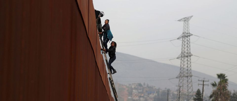 Migrants from Honduras, part of a caravan of thousands from Central America trying to reach the United States, climb a border fence to cross illegally from Mexico to the U.S., in Tijuana, Mexico, December 21, 2018. REUTERS/Mohammed Salem