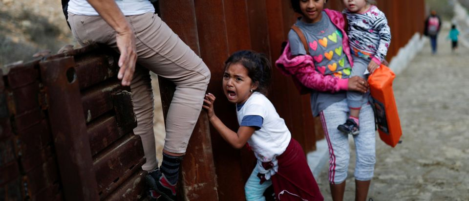 A migrant girl, who is part of a caravan of thousands from Central America trying to reach the United States, cries next to the border wall while she tries to cross illegally with her family from Mexico to the U.S, in Tijuana, Mexico, December 11, 2018. REUTERS/Carlos Garcia Rawlins