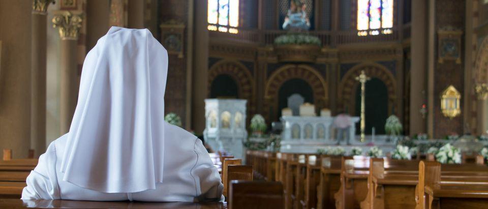 A Nun praying (Shutterstock/Milkovasa)