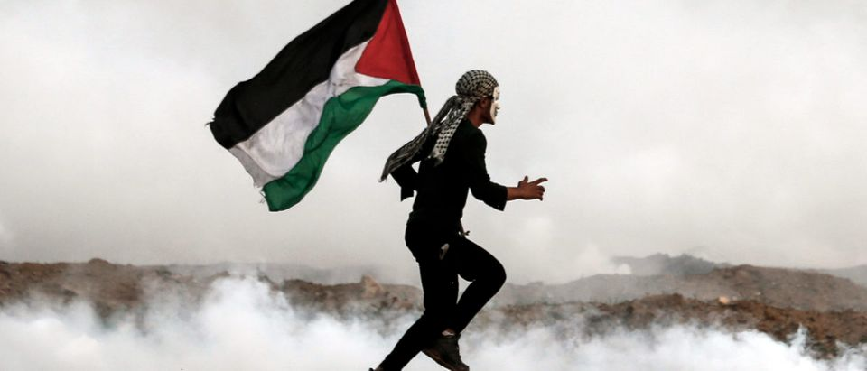A Palestinian man holds the national flag as he runs through teargas during a riot. (Mahmud Hams/AFP/Getty Images)