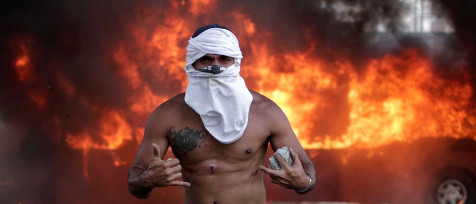 """An opposition demonstrator with wounds gestures in front of a burning bus, while holding a rock, near the Generalisimo Francisco de Miranda Airbase """"La Carlota"""" in Caracas, Venezuela, April 30, 2019. REUTERS/Ueslei Marcelino"""