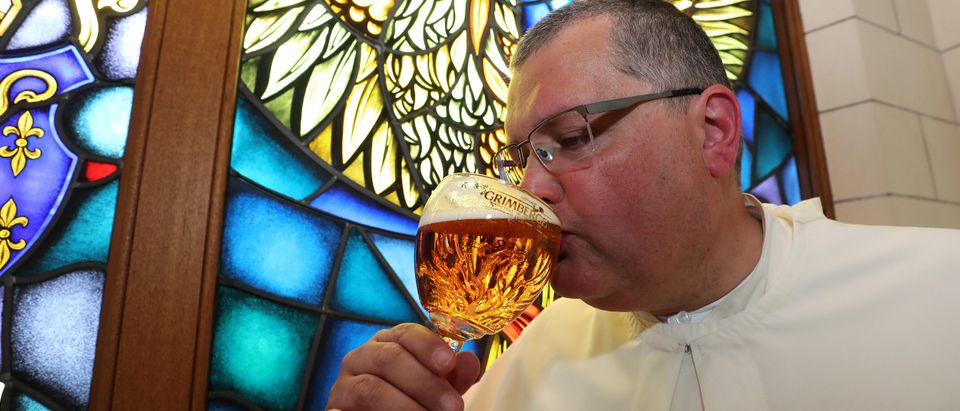 Norbertine Father Karel tastes a Grimbergen beer, symbolised by a phoenix, in the courtyard of the Belgian Abbey of Grimbergen before announcing that the monks will return to brewing after a break of two centuries, in Grimbergen